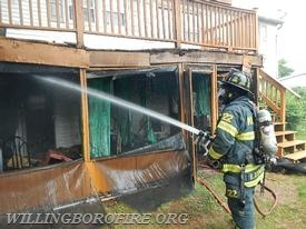 Firefighter E. O'Donnell hosing down the porch area.