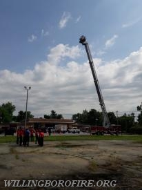 The cadets going up in the bucket of Ladder 1615