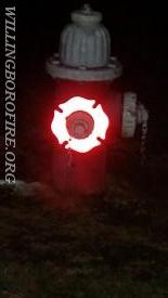 A dark hydrant with light on the marker