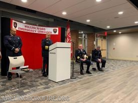 Chief of Department Burnett addresses the crowd as Lieutenant Ferrell, David Andrade, and Firefighter Thomas Boyle look on