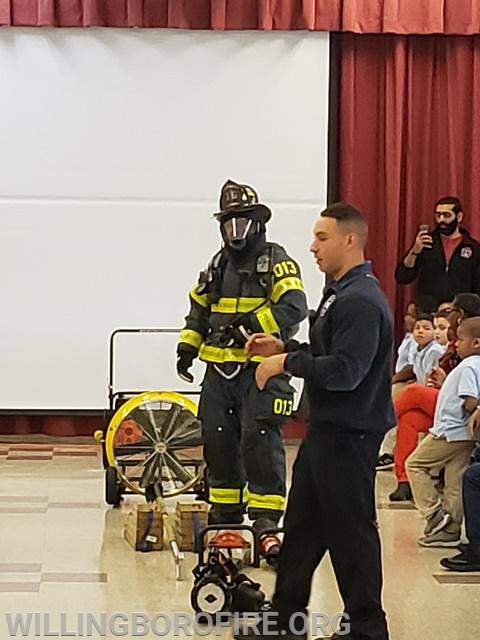 Firefighter Centrone (foreground) speaks to students at Hawthorne Elementary school about the protective equipment Firefighter Lehuquet is wearing