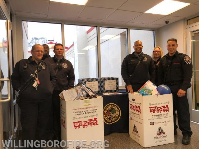 EMT Johnsen, Firefighter Bennett, Captain Gardner, Lieutenant Ferrell, EMT Kasowski, and Firefighter Centrone (L to R) delivering the toys