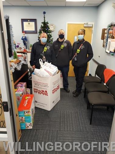 Fire and EMS personnel dropping off Toys for Tots box.