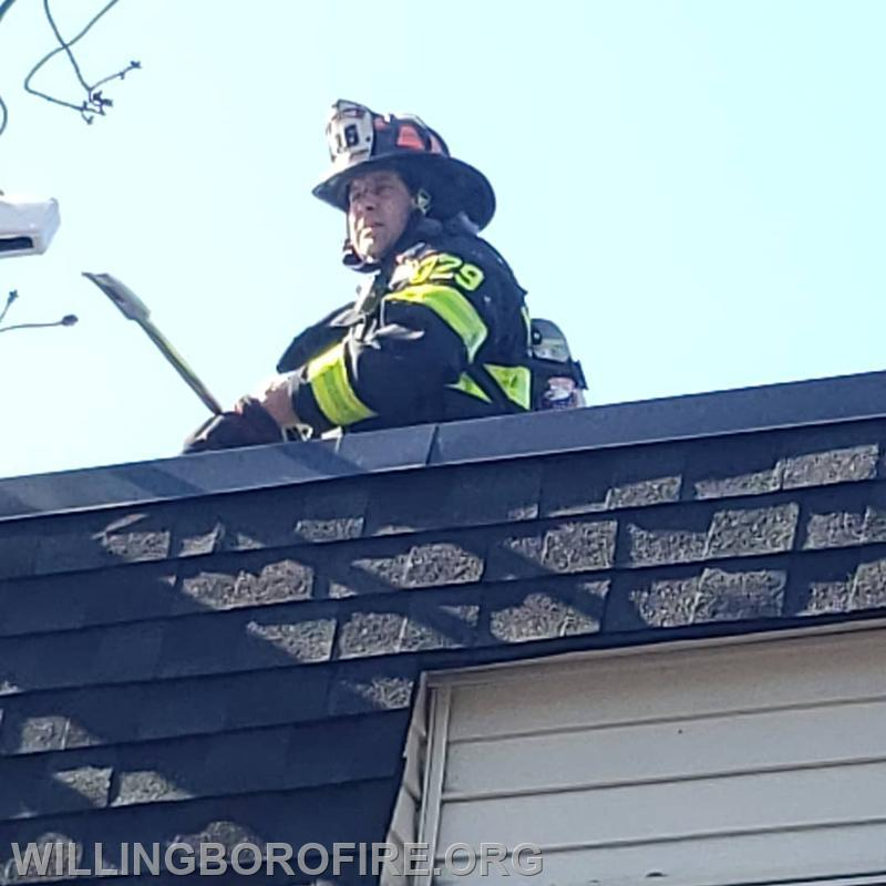 Cap. Friddell checking the roof for fire